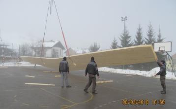 Razlaganje nosilcev na zunanje igrišče, kjer se bodo sestavljali okvirji za nosilno strešno konstrukcijo nove športne dvorane.