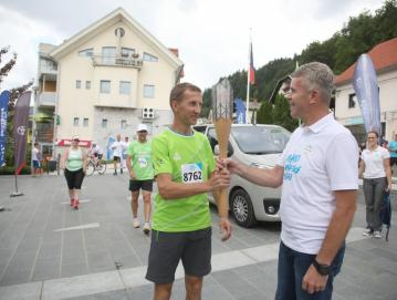 Baklo je na Trgu Ivana Regna iz rok olimpijca Antona Kosmača sprejel župan Milan Čadež. FOTO: GORAZD KAVČIČ