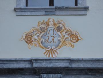 Poslikava nad vhodom v dvorec predstavlja bogato okvirjeno hišno številko.
